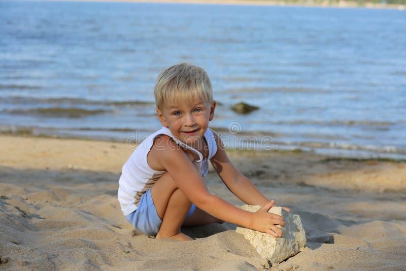 小男孩坐在海滩的沙子在河附近 免版税库存照片