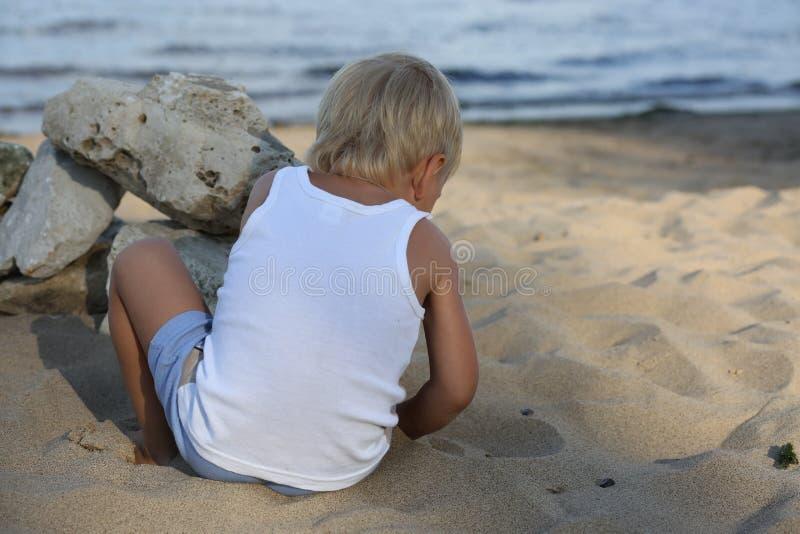 小男孩坐在海滩的沙子在河附近 库存照片