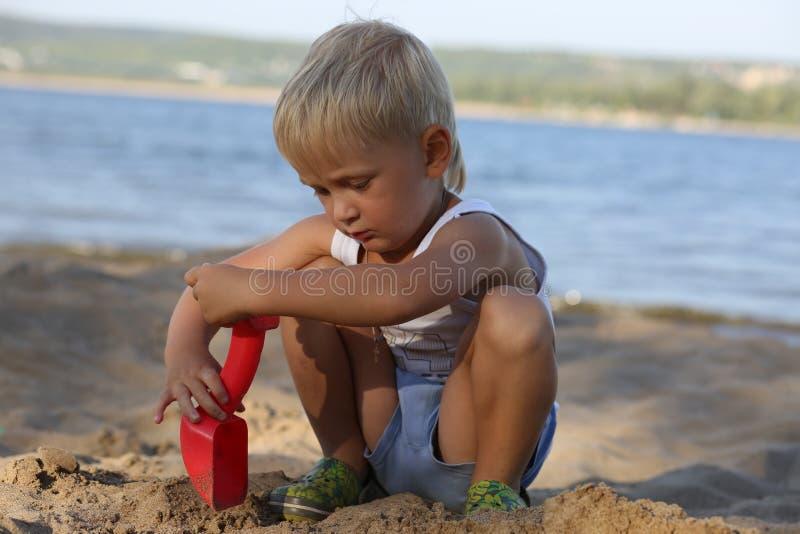 小男孩坐在海滩的沙子在河附近 免版税库存图片