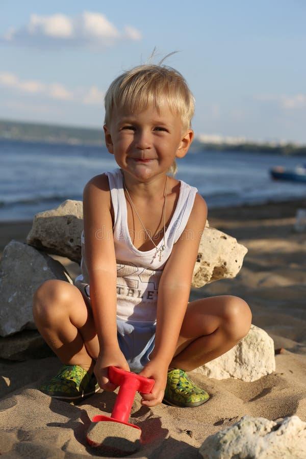 小男孩坐在海滩的沙子在河附近 库存图片