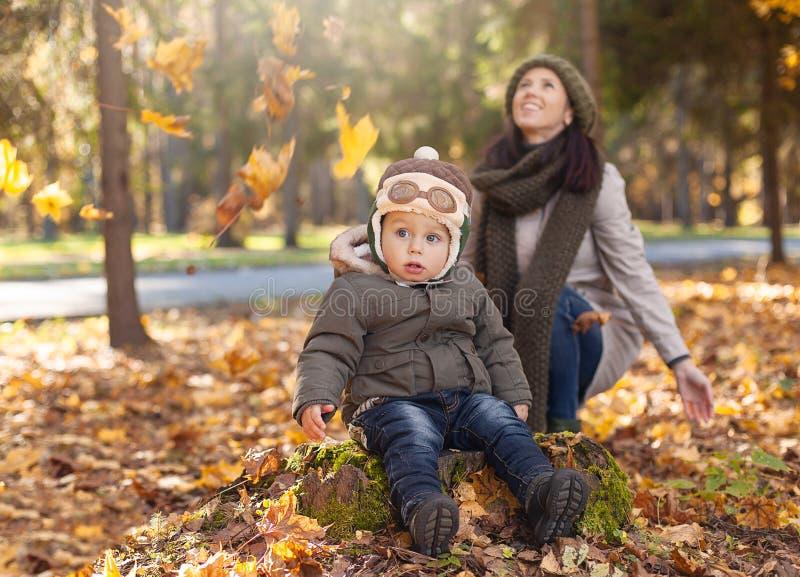 小男孩坐树桩在有传单的母亲附近在公园 图库摄影