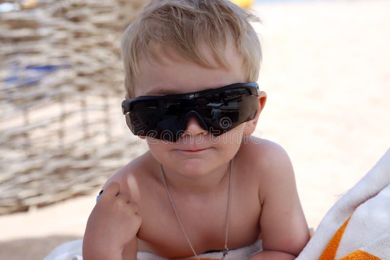 小男孩坐海滩 免版税库存照片