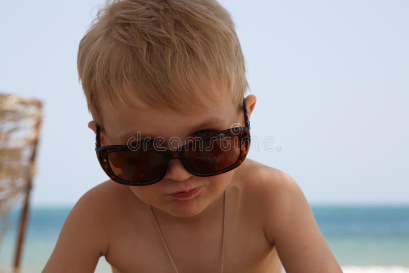 小男孩坐海滩 免版税库存图片