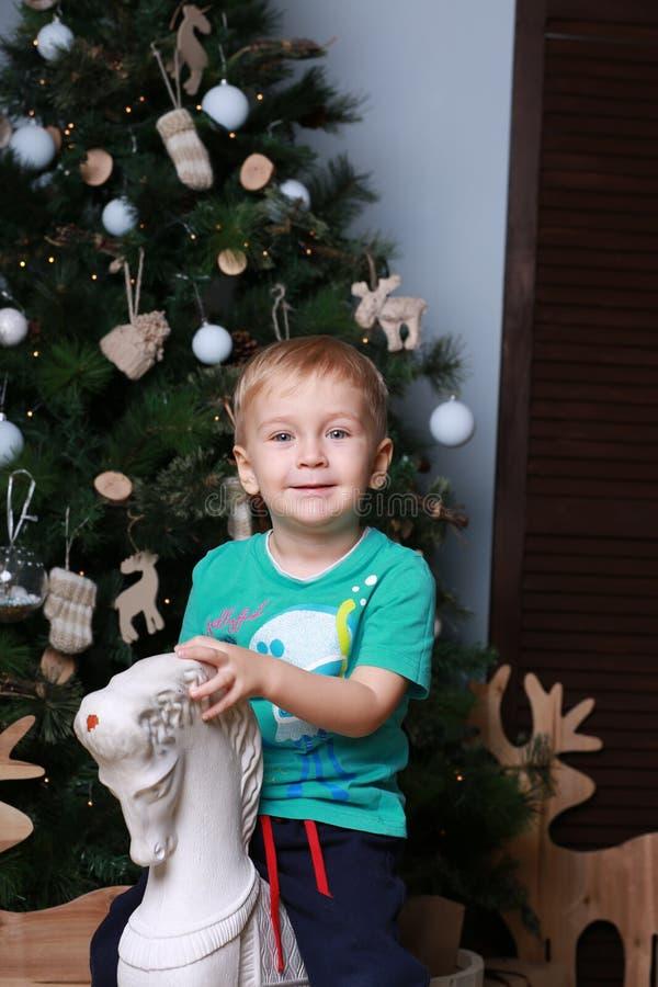 小男孩坐玩具马 免版税库存图片
