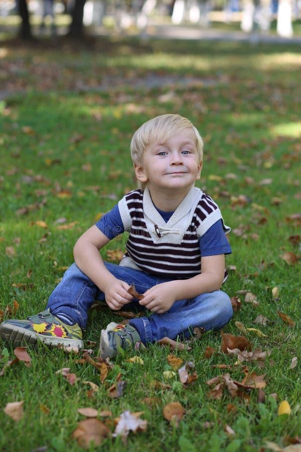 小男孩坐绿草 免版税图库摄影