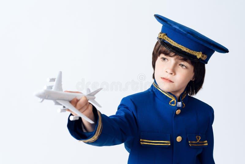 小男孩学会飞行员的行业 他使用与在飞行员的制服的玩具飞机 免版税库存照片