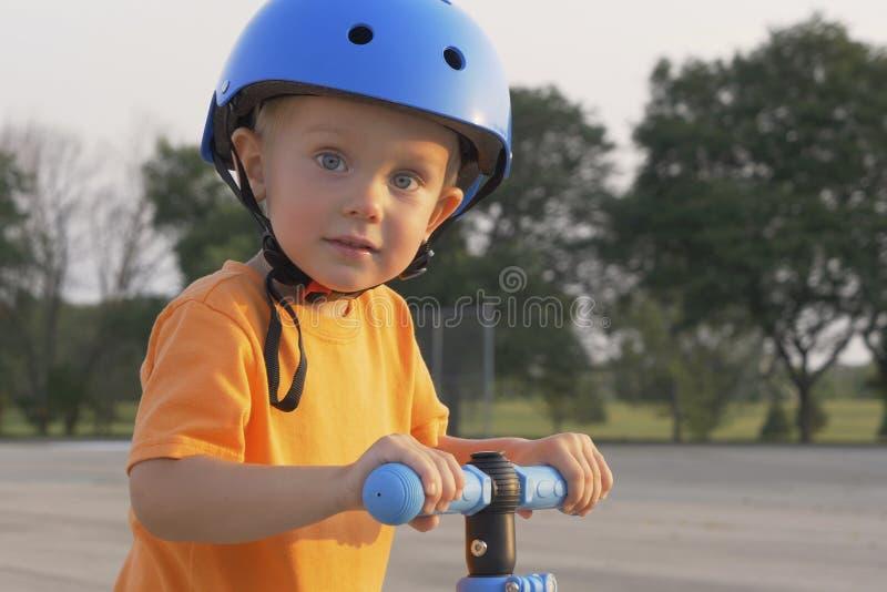小男孩孩子、孩子橙色T恤杉的和蓝盔部队乘坐滑行车 童年记忆,安全和滑稽的经验 免版税库存照片