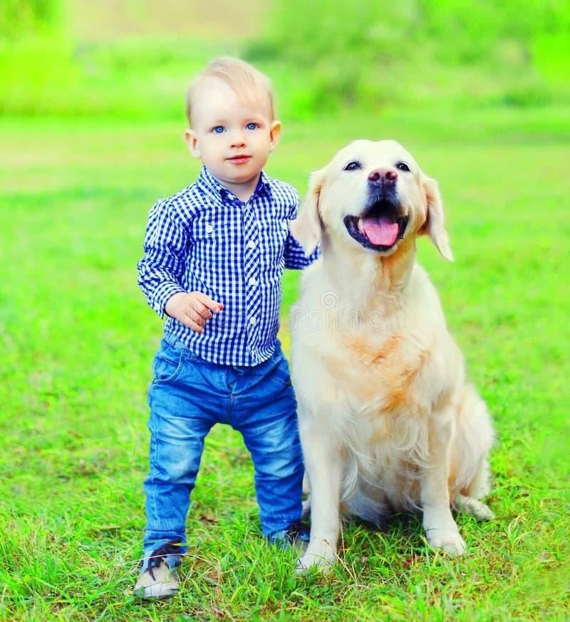 小男孩孩子和金毛猎犬狗在草在夏天停放 库存图片