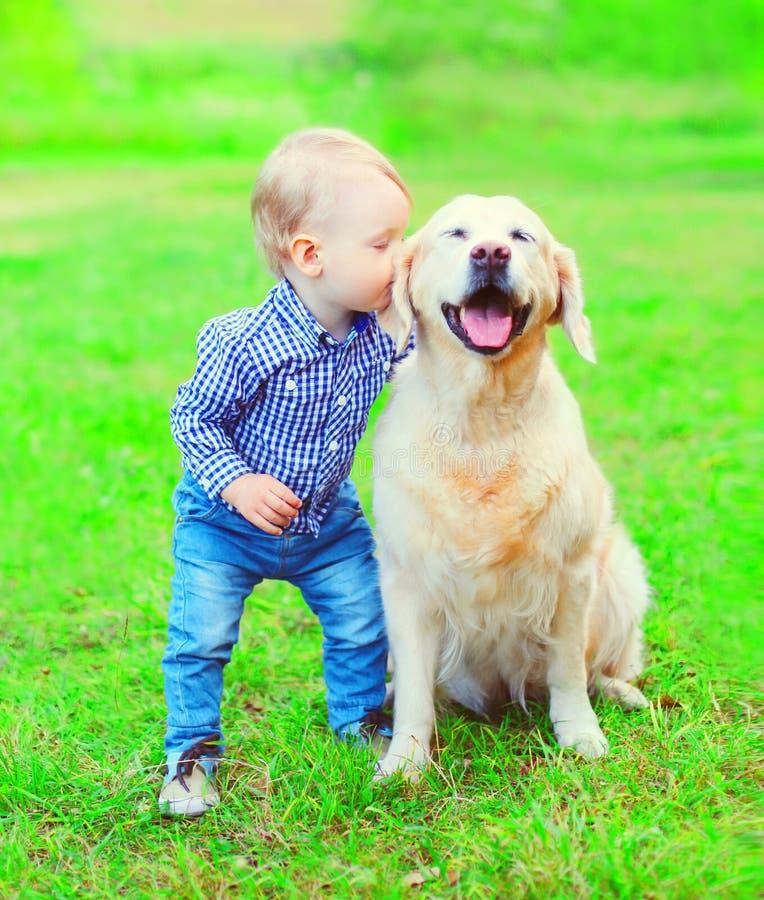 小男孩孩子在公园亲吻在草的金毛猎犬狗 图库摄影
