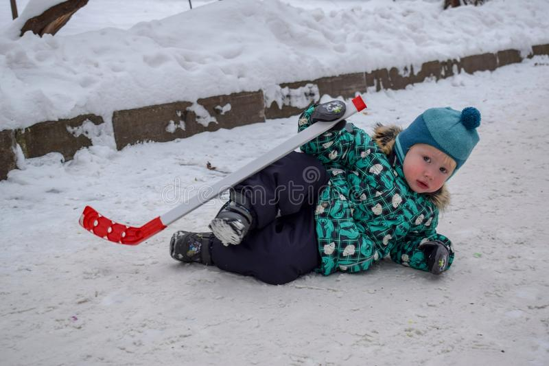 小男孩对打曲棍球是疲乏并且去基于雪用一根棍子在冬天在公园 免版税图库摄影