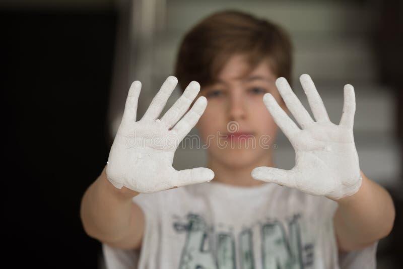 小男孩展示手上涂着白漆 库存图片