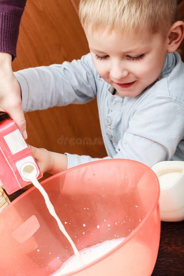 小男孩帮助父母厨师在厨房里 免版税图库摄影