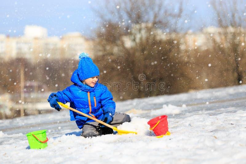 小男孩开掘的雪在冬天,孩子活动 免版税图库摄影