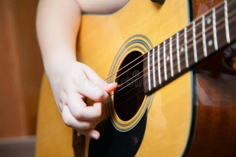 小男孩弹吉他 免版税库存图片
