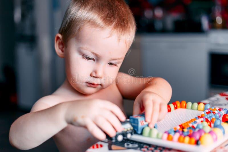 小男孩戏剧在色的桌马赛克的棋 库存照片