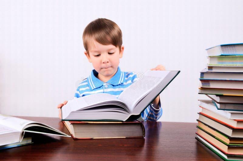 小男孩打开一本大书和调查它 免版税库存图片