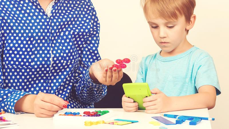 小男孩打逻辑比赛在一个心理学家聪明的孩子的教训与学会在学龄前教室的老师的 教育a 免版税图库摄影