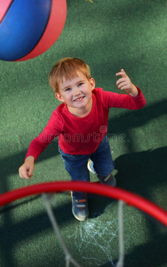 小男孩投掷在圆环的篮球球 免版税库存图片