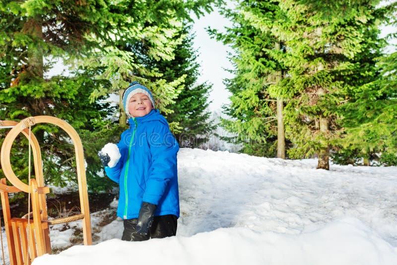 小男孩投掷雪球在公园 免版税库存图片