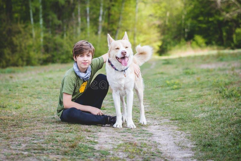 小男孩抱着他的狗 免版税图库摄影