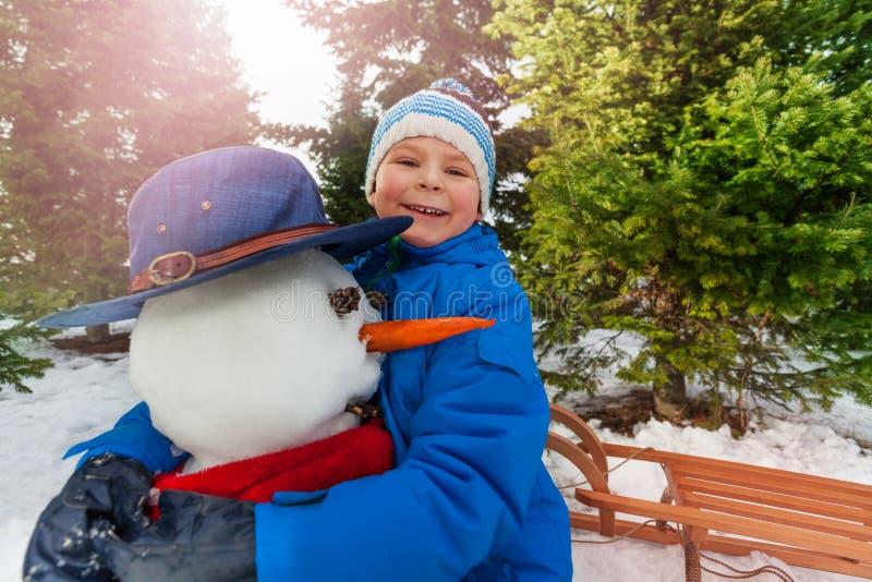 小男孩拥抱雪人在公园和微笑 免版税库存图片