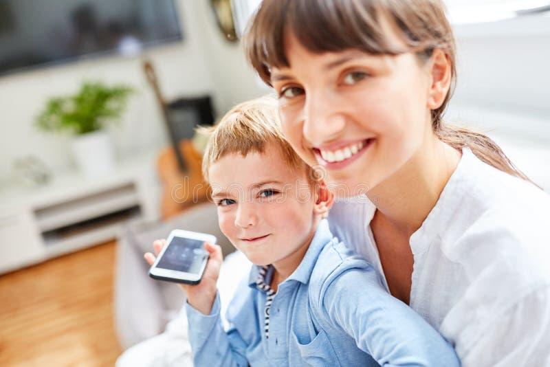 小男孩拿着母亲` s智能手机 免版税库存照片