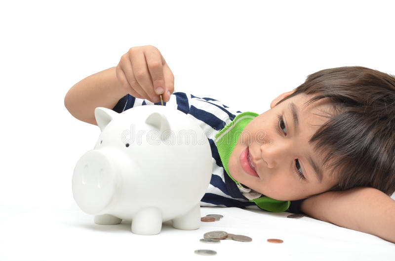 小男孩挽救金钱在存钱罐中 免版税库存图片