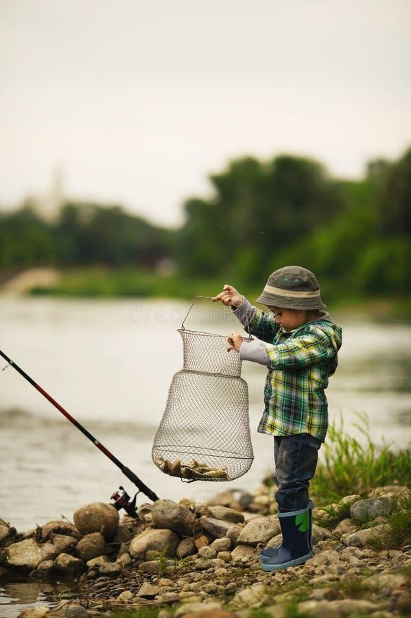 小男孩捕鱼照片  图库摄影
