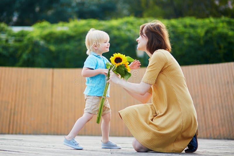 小男孩提供的束对他的妈妈的向日葵 免版税图库摄影