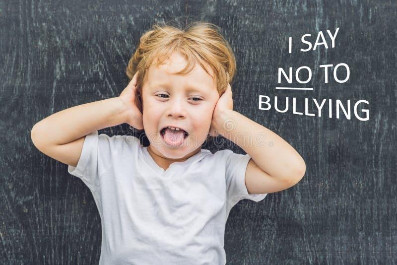 小男孩支持和对胁迫说不通过吹莓在黑板前面的恶霸在schoo 免版税库存照片