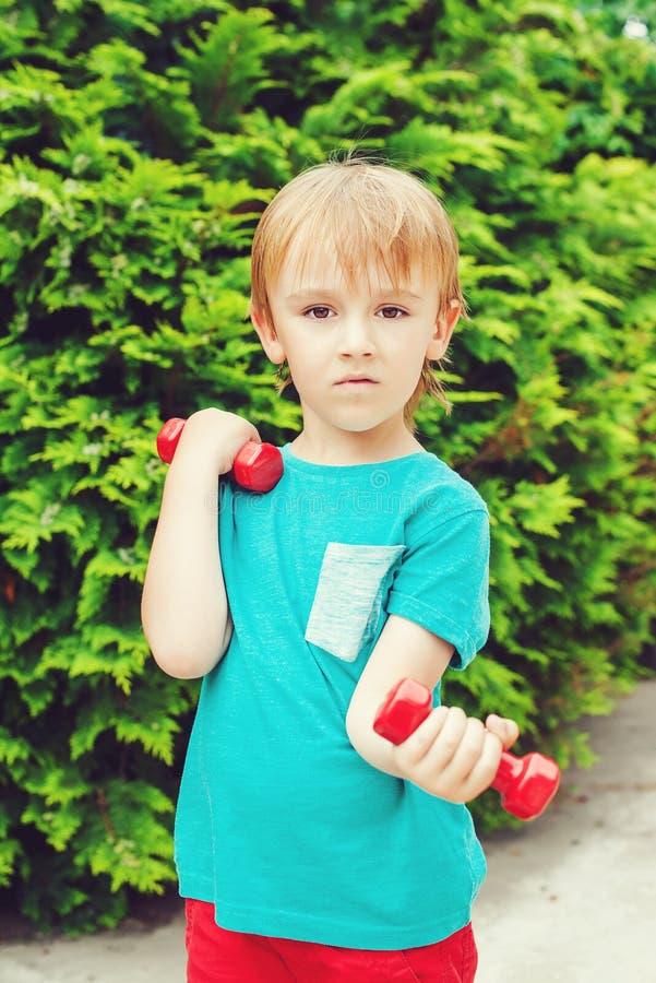 小男孩有行使与室外的哑铃 免版税库存照片
