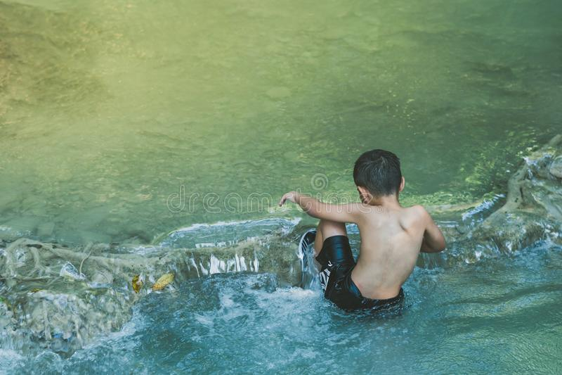 小男孩横穿充分河仔细石头和蹒跚地走在瀑布在爱侣湾国立公园 库存图片
