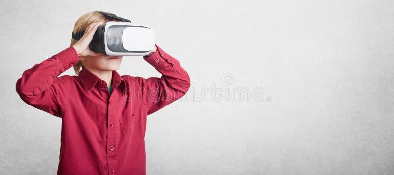 小男孩水平的射击戴VR眼镜,为advertisin看虚拟现实,被隔绝在与拷贝空间的白色背景 库存照片