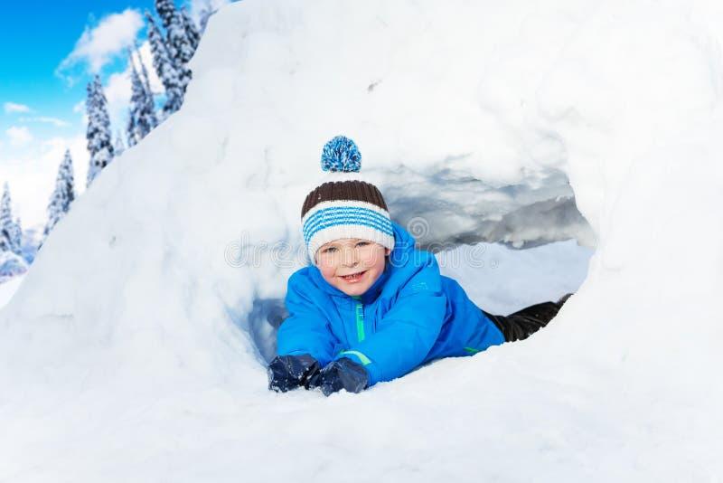 小男孩爬行通过雪隧道在公园 免版税库存照片