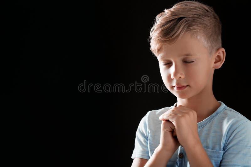 小男孩用为在黑背景的祷告一起扣紧的手 免版税图库摄影