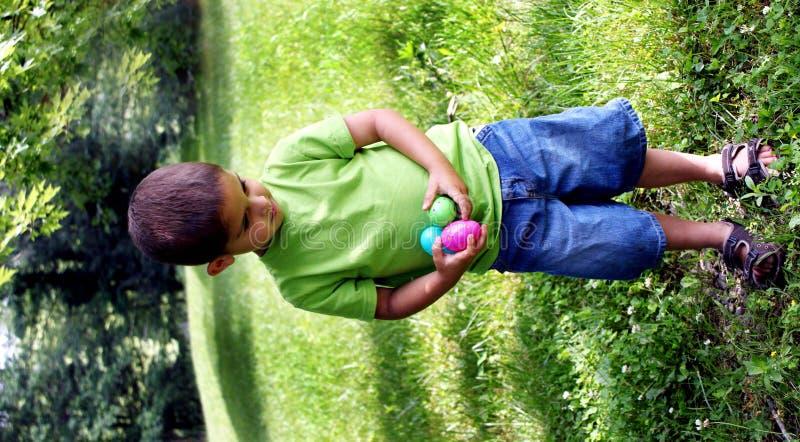 小男孩用在他的现有量的复活节彩蛋 免版税图库摄影