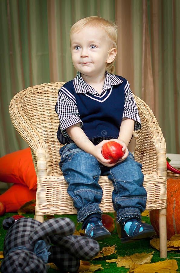 小男孩用苹果坐椅子 库存图片