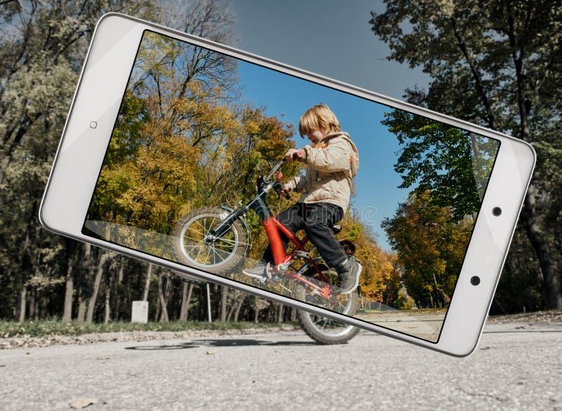 小男孩画象有自行车的在智能手机 库存照片