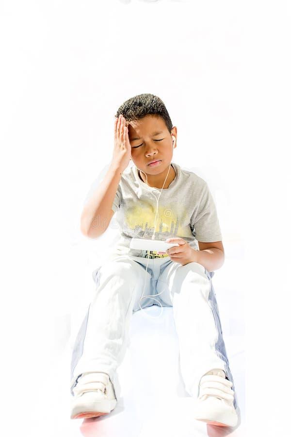 小男孩疲倦了和遭受偏头痛在使用聪明以后 免版税库存照片
