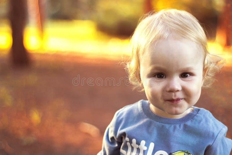 小男孩白发微笑在公园的,秋天 库存照片