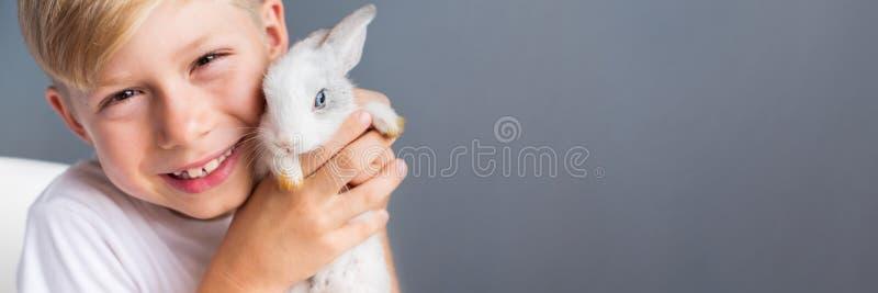 小男孩白色T恤杉和温驯的较矮小兔子 库存图片