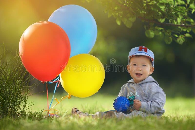 小男孩的第一次生日庆祝在橙色光的一个温暖的夏日 免版税库存照片