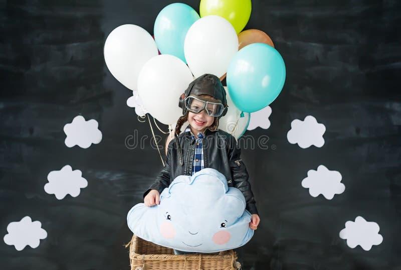 小男孩的画象试验` s衣服的 在气球的飞行 云彩-把枕在手上在男孩 免版税库存图片