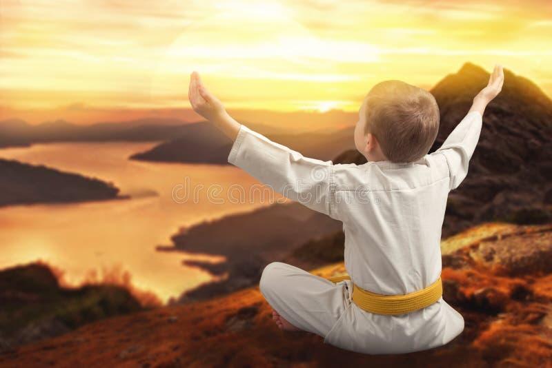 小男孩空手道遇见在山的日出,凝思,训练在山 日本武术 武装精力充沛她