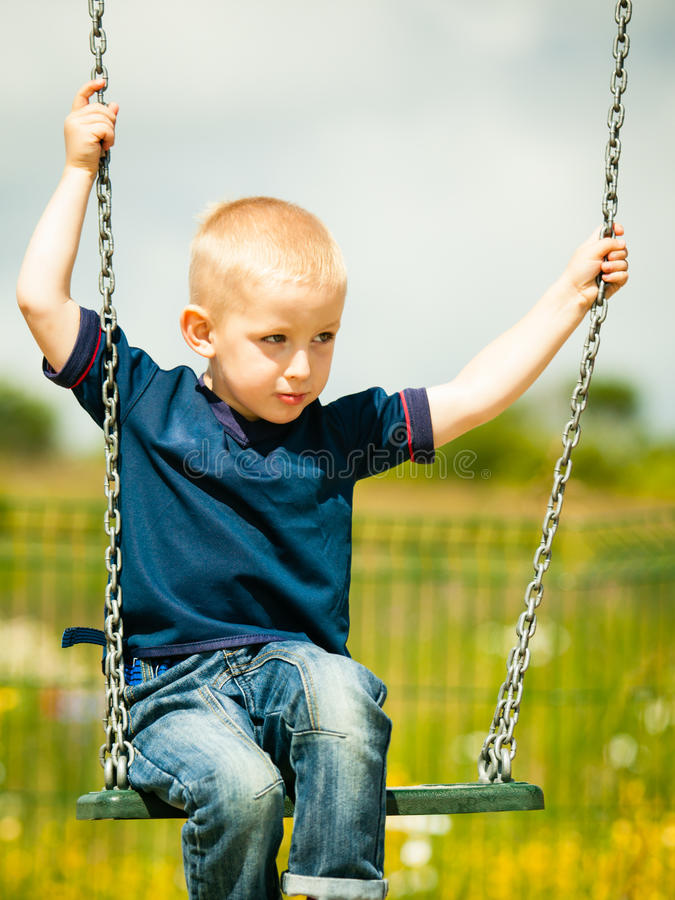 小男孩获得乐趣在操场 使用在摇摆的儿童孩子室外 愉快的活跃童年 免版税图库摄影