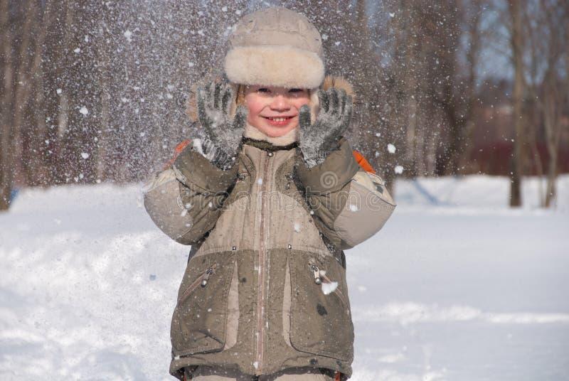 小男孩获得乐趣在雪 免版税图库摄影