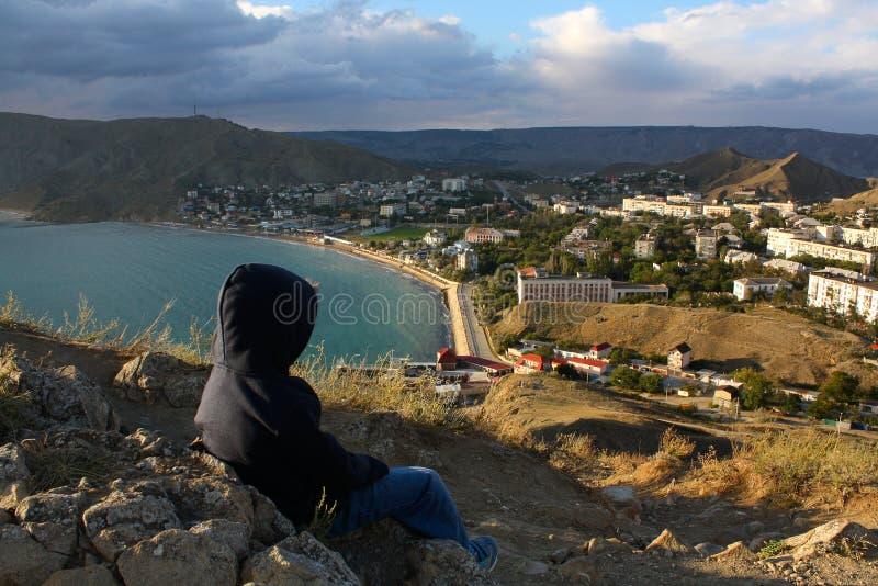小男孩观察海和城市从小山 库存图片
