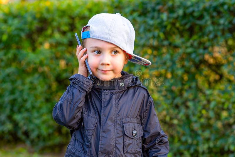 小男孩谈话在电话在公园 童年 免版税库存照片