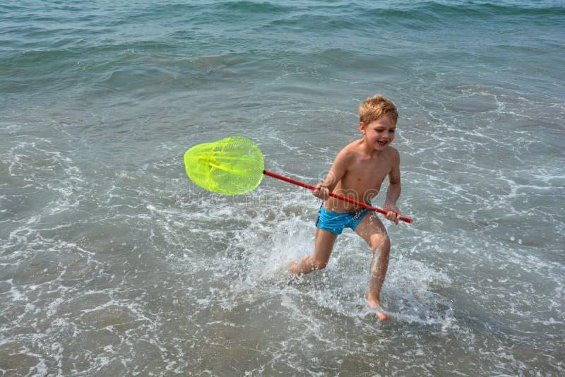 小男孩跑与在海水的渔网 免版税图库摄影