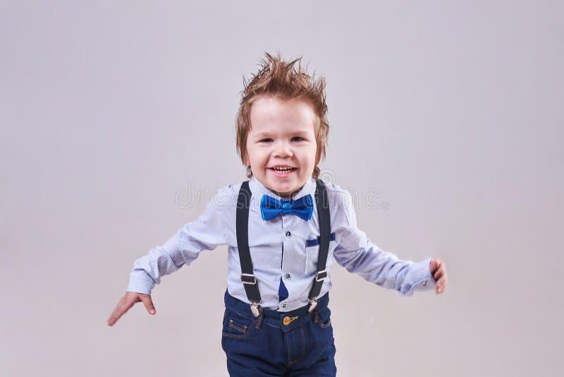 小男孩跑和微笑,穿一个蓝色蝶形领结和悬挂装置 免版税库存照片
